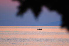 Pêcheur dans le bateau au coucher du soleil Photographie stock libre de droits