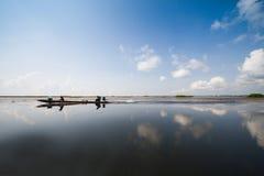Pêcheur dans le bateau en bois crusing dans le lac avec la réflexion avec le fond nuageux de ciel bleu Photo stock