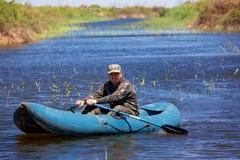 Pêcheur dans le canot en caoutchouc sur le fleuve Photographie stock libre de droits