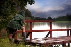 Pêcheur dans le lac orageux Image stock