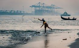 Pêcheur de Kochi de fort jetant son filet dans l'eau Inde photos stock