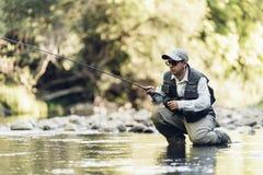Pêcheur de mouche à l'aide de la tige flyfishing Image stock