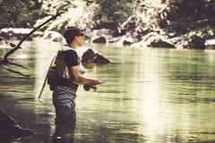 Pêcheur de mouche flyfishing en rivière Photographie stock