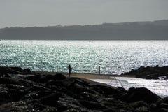 Pêcheur de pêcheur à la ligne de mer s'occupant ses tiges Photo libre de droits