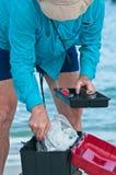 Pêcheur de ressac recherchant dans la boîte à leurres Photographie stock