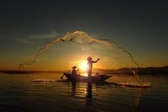 Pêcheur des personnes asiatiques au lac dans l'action en pêchant pendant le lever de soleil image stock
