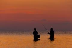 Pêcheur deux restant en mer sur une île tropicale au coucher du soleil Images libres de droits
