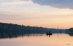 Pêcheur deux sur le bateau au coucher du soleil Image stock