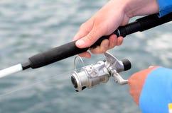 Pêcheur employant une bobine de tige et de fileur Images libres de droits