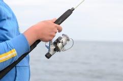 Pêcheur employant une bobine de tige et de fileur Photos stock