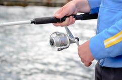 Pêcheur employant une bobine de tige et de fileur Photographie stock libre de droits