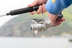 Pêcheur employant une bobine de tige et de fileur Images stock