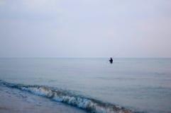 Pêcheur en mer par la plage tôt le matin Photographie stock