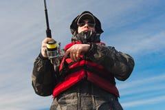 Pêcheur en verres avec un poteau de pêche dans le ciel Image stock