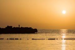 Pêcheur et coucher du soleil Images stock