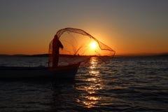 Pêcheur et le coucher du soleil Photographie stock libre de droits