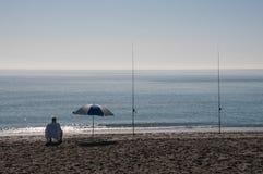 Pêcheur et parasol solitaires de ressac à la plage Image libre de droits