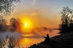 Pêcheur et un coucher du soleil Image libre de droits