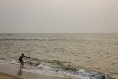 Pêcheur indien avec un filet de pêche sur une plage sablonneuse contre l'océan le soir image libre de droits