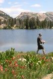 Pêcheur marchant par le bord de lac   Images stock