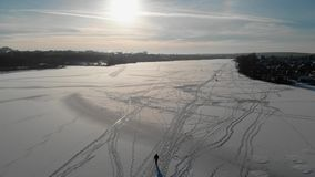 Pêcheur marchant sur une rivière congelée Le dessus regardent vers le bas Ombre d'un homme de marche dans la neige Silhouette d'h clips vidéos