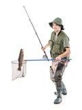 Pêcheur mettant un poisson dans un filet de pêche Photographie stock libre de droits
