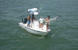 Pêcheur moulant un épervier d'un petit bateau de pêche Image stock