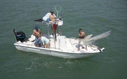 Pêcheur moulant un épervier d'un petit bateau de pêche Photos stock