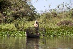 Pêcheur plaçant le piège de poissons près de la rive photographie stock