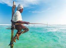 Pêcheur plus âgé d'échasse à la plage de Hikkaduwa Photos libres de droits