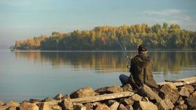 Pêcheur professionnel pêchant sur la berge, la tige et l'attirail, équipement photo libre de droits
