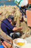 Pêcheur réparant des filets de pêche à un port sicilien Photographie stock libre de droits