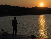 Pêcheur refroidissant contre le beau coucher du soleil en Grèce Image libre de droits