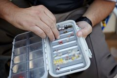 Pêcheur sélectionnant une mouche d'une boîte à leurres Images libres de droits