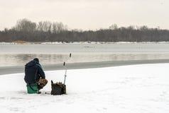 Pêcheur s'asseyant sur une banquise et pêchant dans le trou images stock