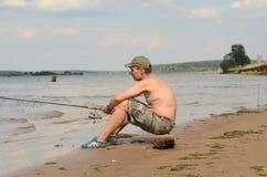 Pêcheur s'asseyant sur une côte Photographie stock
