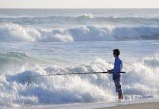 Pêcheur se tenant dans l'eau Images stock
