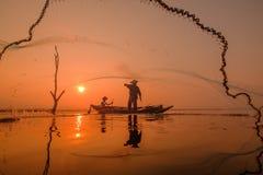 Pêcheur se tenant sur un bateau de pêche pour un poisson dans l'eau Images stock
