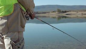 Pêcheur Sits With Rod In The Water Reservoir et un poisson de pêche d'accrochage banque de vidéos
