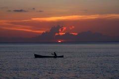 Pêcheur solitaire au coucher du soleil Photos stock