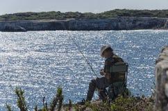 Pêcheur solitaire occupé dans la préparation d'amorce Photo stock