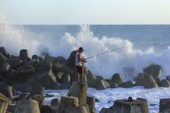 Pêcheur Stands sur des vagues de brise-lames Images stock