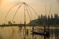 Pêcheur sur la pêche de bateau à l'aide des outils nets traditionnels de pêche Images stock