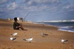 Pêcheur sur le bâti de ressac de plage Photographie stock libre de droits