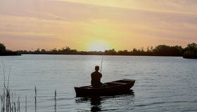 Pêcheur sur le bateau de pêche en rivière Images libres de droits