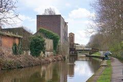 Pêcheur sur le chemin de canalside, vieux bâtiments industriels, Charger-sur-Trent Image libre de droits