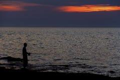 Pêcheur sur le coucher du soleil Image stock