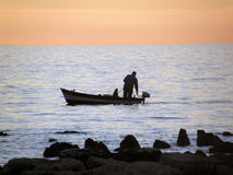 Pêcheur sur le coucher du soleil Photographie stock libre de droits