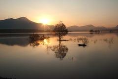 Pêcheur sur le grand lac en matin. photographie stock
