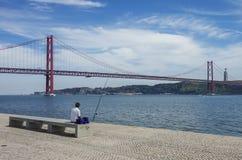 Pêcheur sur le remblai de la rivière de Tejo avec les 25 De Abril Bridg Image stock